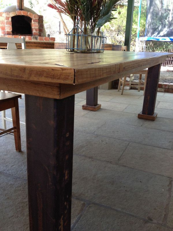 Reclaimed timber table with rusted industrial steel legs.